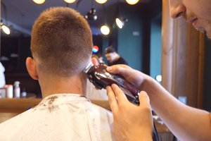 Man barber cutting hair of male client with clipper at barber shop. Hairstyling process. Slow motion Close up