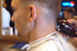 Man barber cutting hair at neck of male client with clipper at barber shop. Hairstyling process. Slow motion Close up
