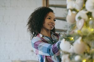 Attractive young African woman decorating Christmas tree at home preparing for Xmas celebration