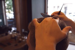 Man barber cutting hair of male client using scissor and comb in barbershop. Hairstyling process. Slow motion Close up