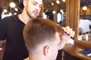 Hair styling process. Man barber doing combing hair to his male client in barber shop. Slow motion Close up