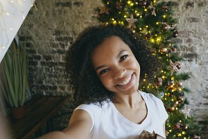 Funny mixed race girl taking selfie pictures on smartphone camera at home near Christmas tree