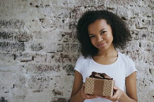 Portrait of Young happy african girl holding gift box and smiling into camera