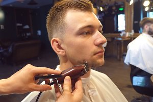 Trimming beard of male client with clipper at barber shop. Hairstyling process. Close up Slow motion