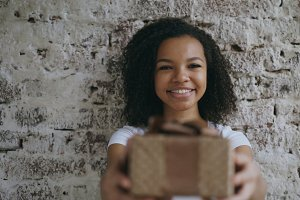 Portrait of Young happy african girl present gift box and smiling into camera