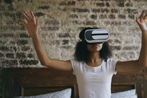 Curly african american woman getting experience using VR 360 headset glasses of virtual reality at home