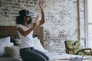 Curly mixed race teenager girl getting experience using VR 360 headset glasses of virtual reality at home
