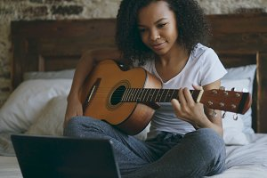 Attractive african american teenager girl concentraing learning to play guitar using laptop computer sitting on bed at home
