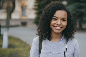 Portrait of mixed race curly student girl smiling into camera and laughing at city street
