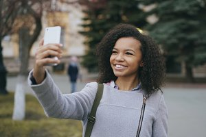 Cheerful mixed race student girl talking at video call with smartphone near univercity