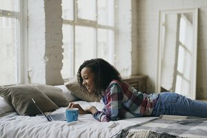 Curly mixed race student girl lauging using laptop for sharing social media lying in bed at home