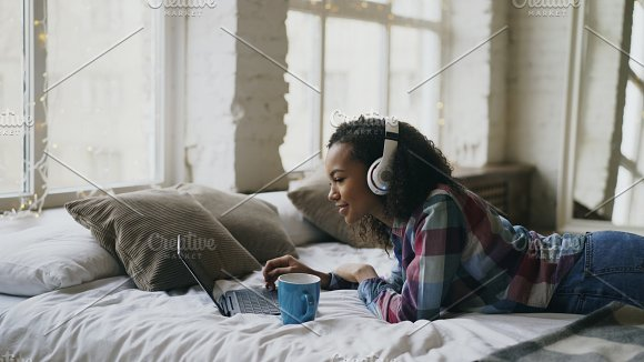Attractive mixed race girl listen to music while surfing social media on laptop lying on bed