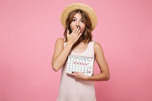 Portrait of a shocked overwhelmed girl in summer hat