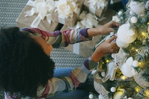 Top view of Attractive young African woman decorating Christmas tree at home preparing for Xmas celebration