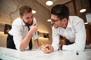 Two young happy businessmen working on a business plan