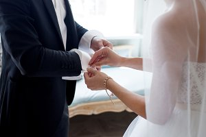 The bride helps her fiance to fasten