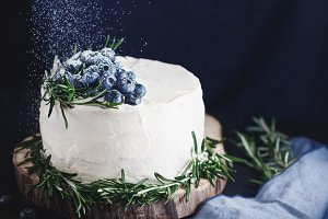 The white cream cake with fresh blueberries is sprinkled with powdered sugar
