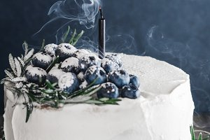The white cream cake with fresh blueberries on birthday and the black extinguished candle with smoke.