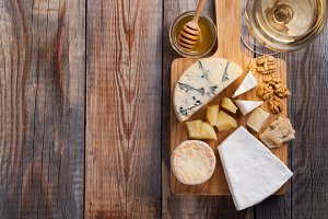 Tasting cheese dish on a wooden plate. Food for wine and romantic, cheese delicatessen on a wooden rustic table. Top view with copy space
