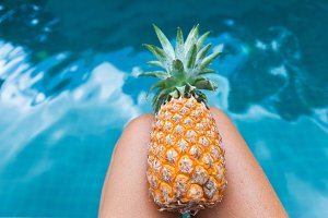 Fresh yellow pineapple tropic fruit summer woman carrying near pool