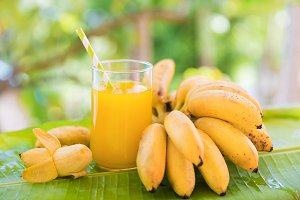 Bunch of bananas on leaf with smoothie juice drink in glass