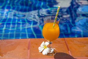 orange juice near swimming pool