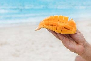 Mango fruit in hand on beach