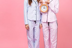 Displeased friends women in pajamas holding alarm clock