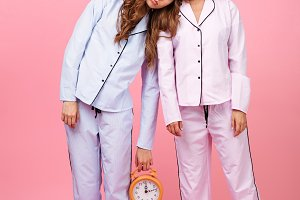 Friends women in pajamas isolated over pink background sleeping.
