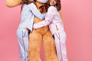 Cheerful friends women in pajamas hug big teddy toy bear