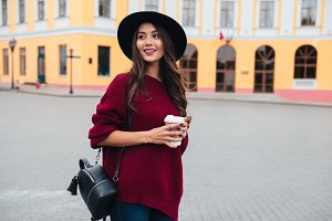 Smiling brunette woman in hat and sweater standing outdoors