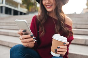 Cropped image of smiling brunette woman in hat and sweater