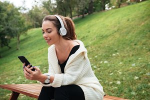 Young happy lady sitting in park chatting by phone
