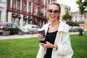 Happy woman walking outdoors drinking coffee