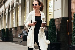 Cheerful lady walking outdoors drinking coffee holding phone.