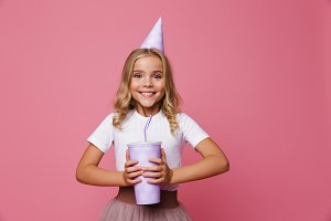 Portrait of a cheerful little girl in a birthday hat