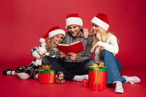 Happy young family wearing christmas hats sitting isolated