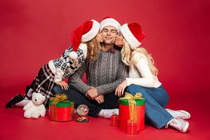 Cute cheerful young family wearing christmas hats sitting isolated
