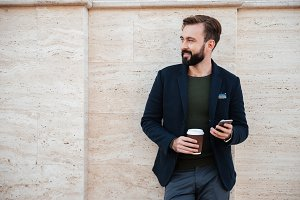 Portrait of a handsome smiling man holding coffee cup
