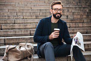 Happy young bearded man sitting outdoors on steps