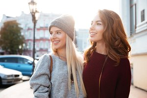 Portrait of two pretty young girls standing on a city street