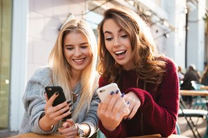 Two excited cheerful girls using mobile phones