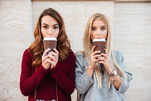 Portrait of a two pretty shocked girls holding coffee cups