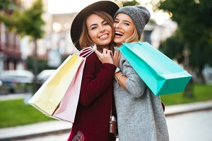 Portrait of two cheerful young girls holding shopping bags