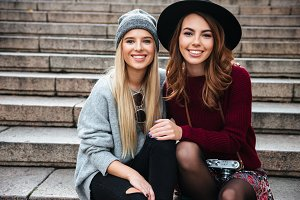 Portrait of two smiling cheerful girls sitting on a staircase
