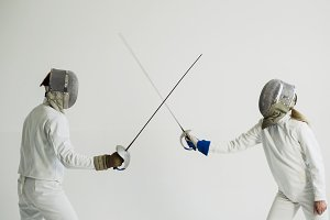 Two fencers having break after training attack exercises in fencing in studio indoors