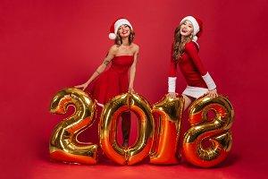 Full length portrait of two happy women in shiny dresses