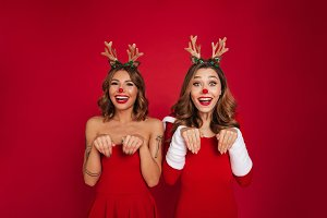 Funny young women friends wearing christmas deer costumes