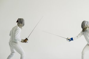 Two fencers have fencing training on white background
