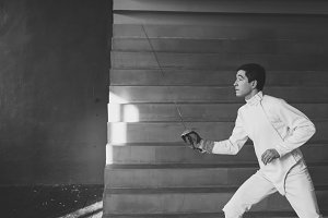Young concentrated fencer man practice fencing exercises and training for Olympic games competition in studio indoors